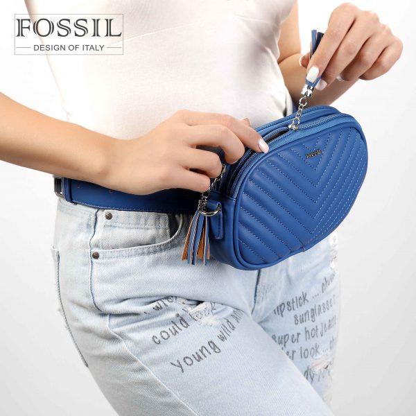 کیف کمری زنانه کد TB-6151 برند فسیل رنگ آبی در دست مانکن خانم